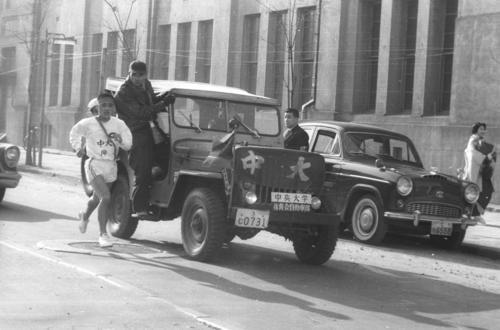 第35回大会 復路10区 日大の追走を振り切らんと伴走車から身を乗り出してアンカー奥宮和文(左=1年)に声を掛ける中大・西内文夫監督(1959年1月3日)