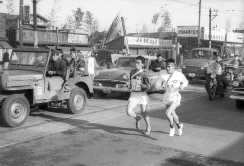 第36回大会 往路2区 5秒差トップでタスキをもらった中大・二宮隆明(右=4年)と日大・武内修一郎(左=3年)の抜きつ抜かれつの激しい首位争い、戸塚中継所800メートル手前でスパートした日大・武内は7秒差をつけ1時間1分58秒の区間新(1960年1月2日)
