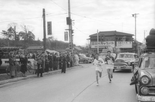 第36回大会 往路3区 7秒差トップでタスキをもらった日大・橋本盛広(右=1年)と中大・南館正行(左=2年)とのデッドヒートは遊行寺の坂を下って藤沢市街へ(1960年1月2日)
