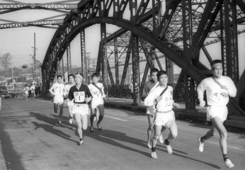 第36回大会 往路1区 八ツ山橋を渡る先頭集団、右端は区間トップとなる中大・田中光城(3年)(1960年1月2日)