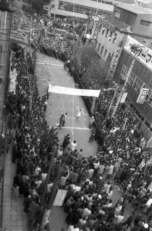 第36回大会 復路10区読売新聞社横ゴール 人、人、人の波の中に歓呼を浴びて中大のアンカー奥宮和文(2年)は2年連続9度目の優勝ゴール、大会史上初の12時間の壁を破る11時間59分33秒の大記録を樹立した(1960年1月3日)