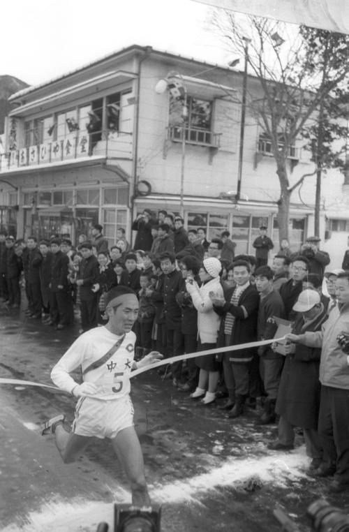 第38回大会 往路5区郵便局前 4連覇を目指す中大は、1区からトップを譲ることなく2位法大に3分45秒差をつけ往路アンカー中島輝雄(2年)がゴール(1962年1月2日)