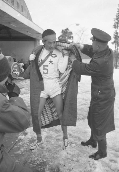 第38回大会 往路5区郵便局前 トップでゴールした往路アンカー中島輝雄(2年)は、寒さの中どてらを着せてもらう(1962年1月2日)