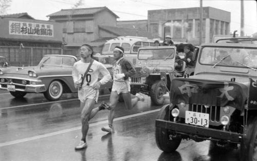 第40回大会 復路10区 往路に続き日大と激しい首位争いを演じた中大は、鶴見中継所での2分17秒差を若松軍蔵(左=2年)が高野俊雄(右=4年)を南品川付近でとらえ抜き去る(1964年1月3日)