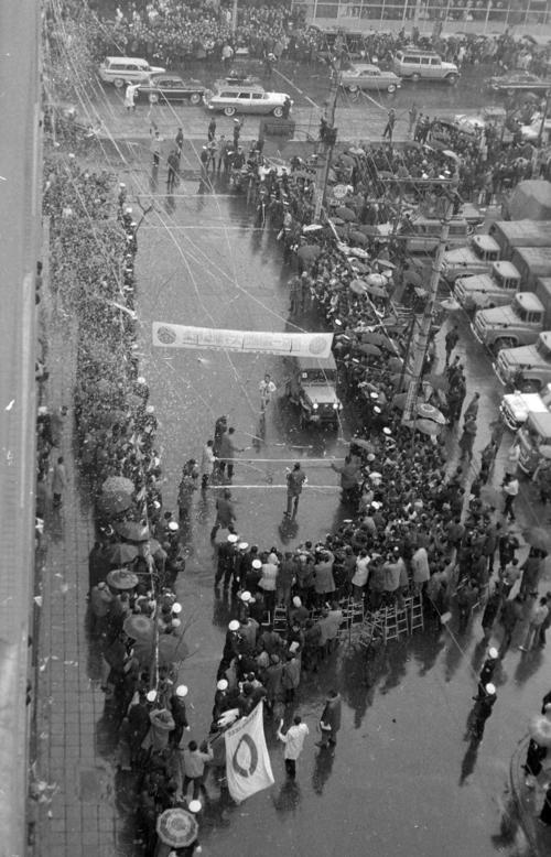 第40回大会 復路10区読売新聞社横ゴール 日大と激しい首位争いを演じた中大のアンカー若松軍蔵(2年)は、みぞれに交じり紙吹雪が舞うゴールへ、中大は11時間33分34秒の新記録で6連覇(通算13度目)を達成(1964年1月3日)