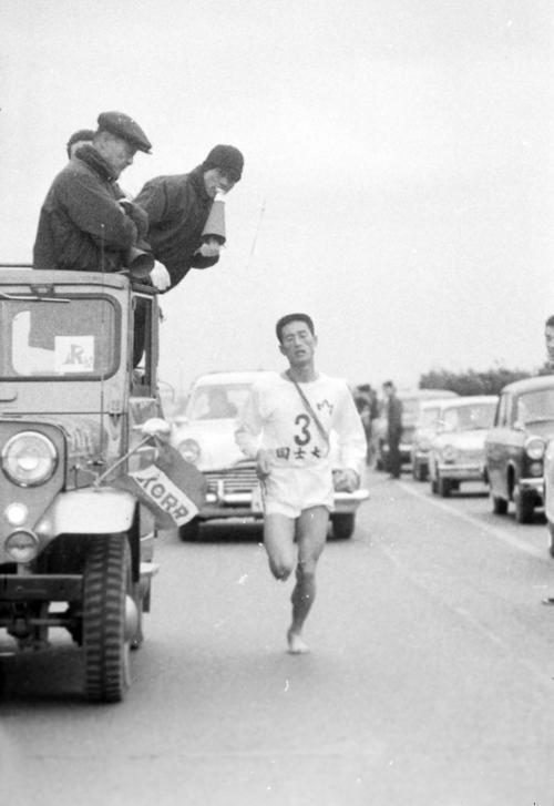 第40回大会 往路3区 4位でタスキをもらった国士舘大・村上孫晴(4年)は辻堂あたりで、履いていたシューズを脱ぎ捨て裸足で力走、1時間2分43秒の区間新で2位に浮上(1964年1月2日)
