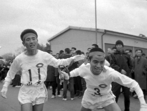 第40回大会 3区戸塚中継所 中大の2区、碓井哲雄(左)から2位でタスキをもらう師岡溢哺(右)(1964年1月2日)