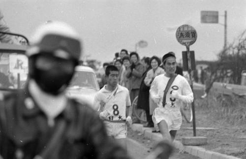 第40回大会 復路8区 11秒差のトップでタスキをもらった日大・高橋英雄(左=1年)は、同郷のライバル中大・福盛祐三(右=1年)にすぐピタリとつかれたが、遊行寺の坂で猛スパートし1分43秒差をつけ戸塚中継所へ(1964年1月3日)