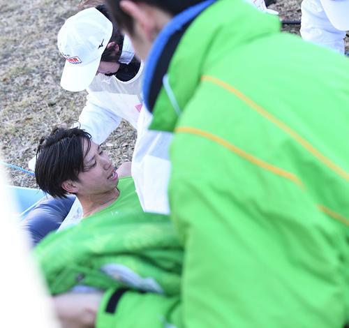 鶴見中継所22位でたすきをつないだ後、倒れ込み運ばれる大東大1区新井(撮影・鈴木みどり)