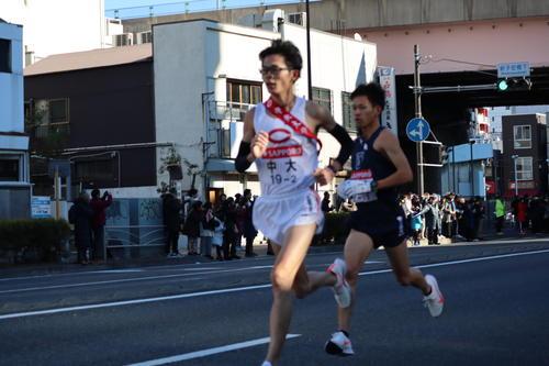 新子安駅前で首位争いする中大・堀尾(左)と東洋大・山本(撮影・横山元保)