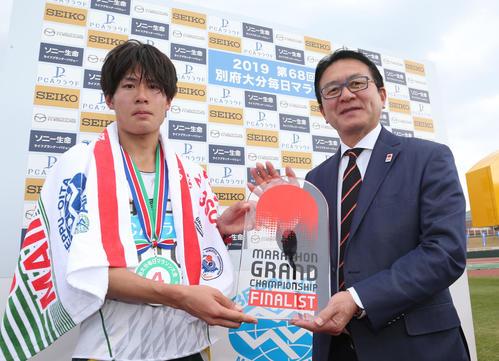 総合4位、日本人1位でゴールした二岡康平はマラソン・グランドチャンピオンシップの出場権を獲得。瀬古利彦氏(右)からチケットを受ける(撮影・梅根麻紀)