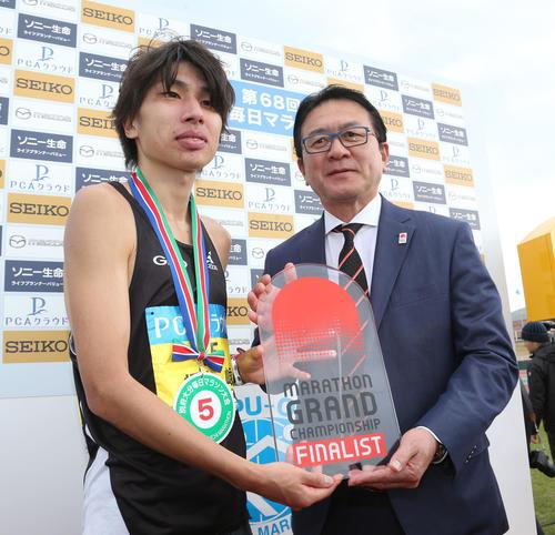 総合5位、日本人2位でゴールした橋本崚はマラソングランドチャンピオンシップシリーズの出場権を獲得。瀬古利彦氏(右)からチケットを受ける(撮影・梅根麻紀)