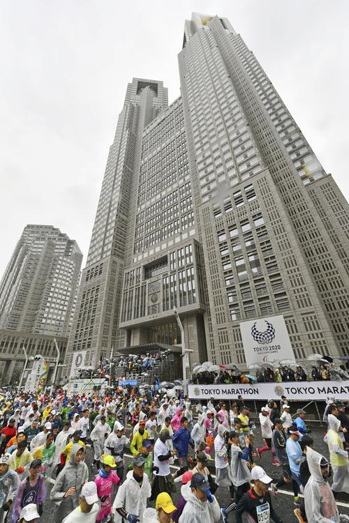 東京マラソンで都庁前を一斉にスタートするランナー(共同)