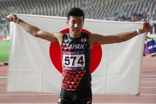 アジア選手権男子100メートルで初優勝を飾り、日の丸を掲げる桐生(ロイター)
