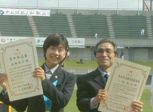 2000年10月16日、富山国体の陸上競技会場で表彰された女子マラソンの高橋尚子は、国民栄誉賞授与に関し快諾の意向を示した。右は小出義雄監督