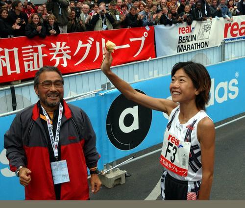 2002年9月29日、ベルリンマラソン2連覇した高橋尚子はゴールの後、黄色いバラを上げ声援にこたえる。左は小出義雄監督
