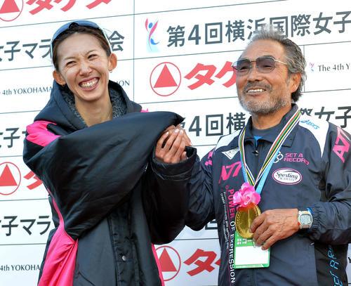 2012年11月18日、横浜国際女子マラソン日本人トップの2位となった那須川(左)は小出監督に用意していたチョコレートでできた金メダルをプレゼントする