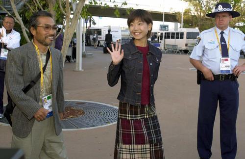 2000年9月15日、シドニー入りし詰めかけた報道陣やファンに手を振りながらバスに向かう五輪マラソン代表の高橋尚子(右)と小出義雄監督