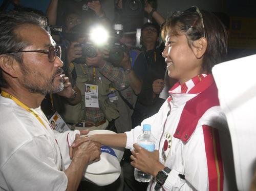 2000年9月24日、シドニー五輪女子マラソンで金メダルを獲得し会見を終えた高橋尚子(右)は待ち受けた小出義雄監督とあらためて握手を交わす