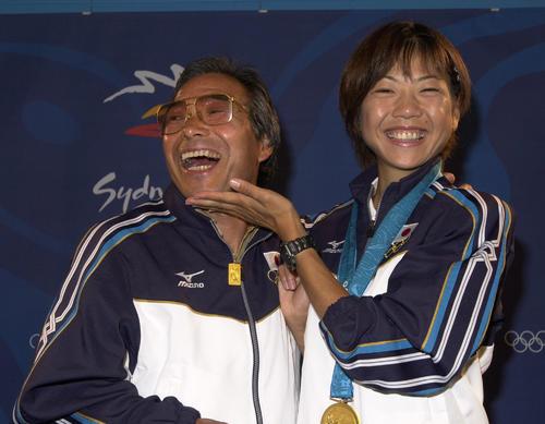 2000年9月24日、シドニー五輪女子マラソンで金メダルを獲得し表彰式のあとに会見した高橋尚子(右)はヒゲを剃った小出義雄監督のアゴをなでて笑顔
