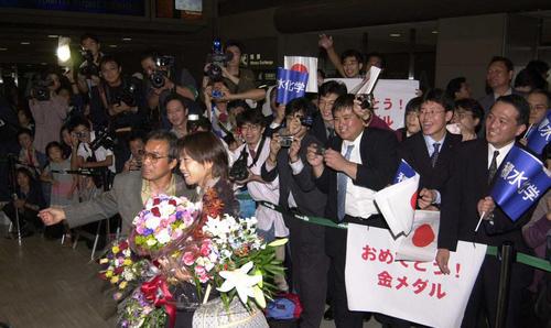 2000年10月2日、シドニー五輪女子マラソンで金メダルを獲得し帰国した高橋尚子と小出義雄監督(左)は出迎えにきた多くのファンと記念撮影