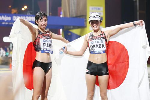 女子20キロ競歩、ゴール後に日の丸を手に笑顔の岡田(右)と藤井(撮影・河野匠)