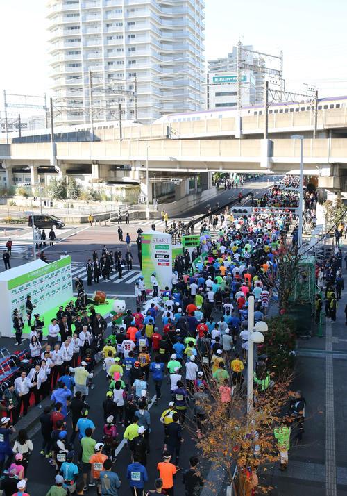 新幹線が通過する中、いっせいにスタートするフルマラソン一般の部の参加者たち(撮影・河野匠)
