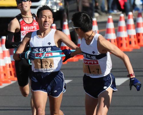 2019年大会で旭化成6区の市田宏(左)からトップでタスキを受け取る7区の大六野秀畝