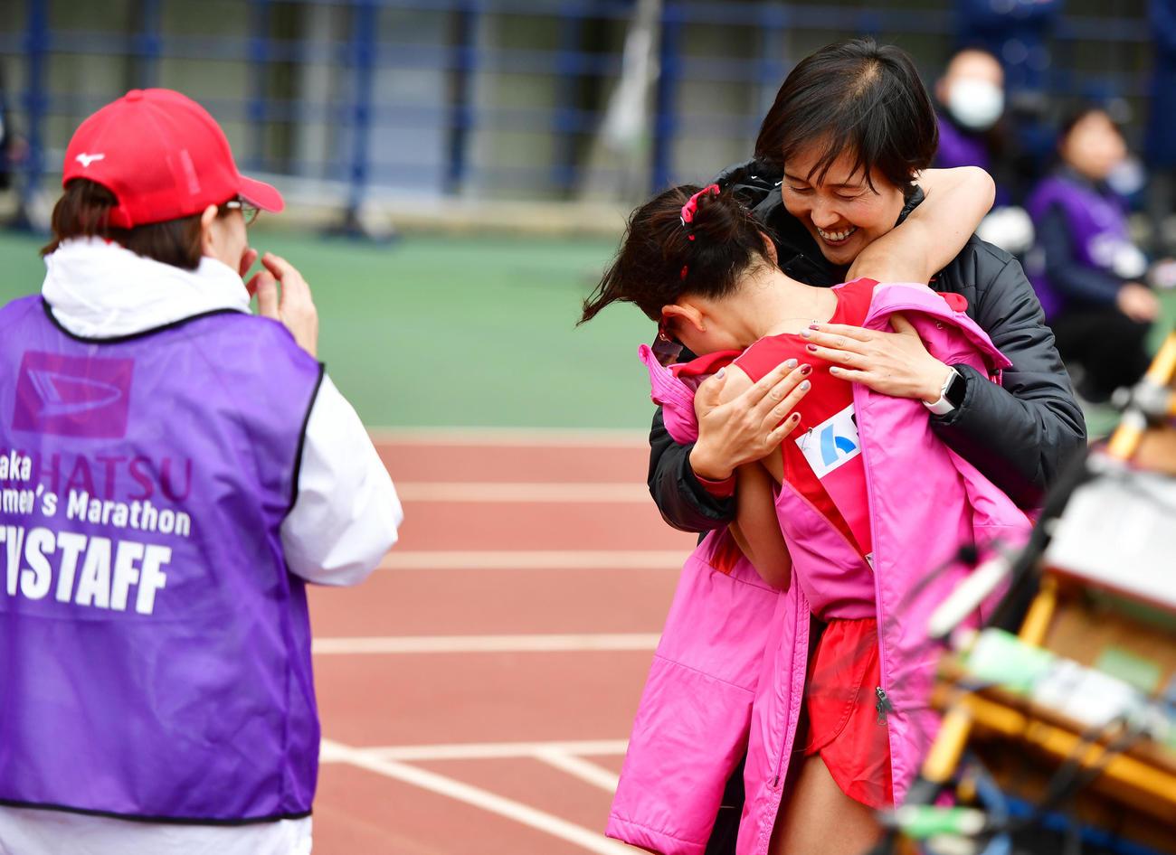 2時間21分47秒で優勝しダイハツ山中美和子監督(右奥)と抱き合う松田瑞生(撮影・清水貴仁)
