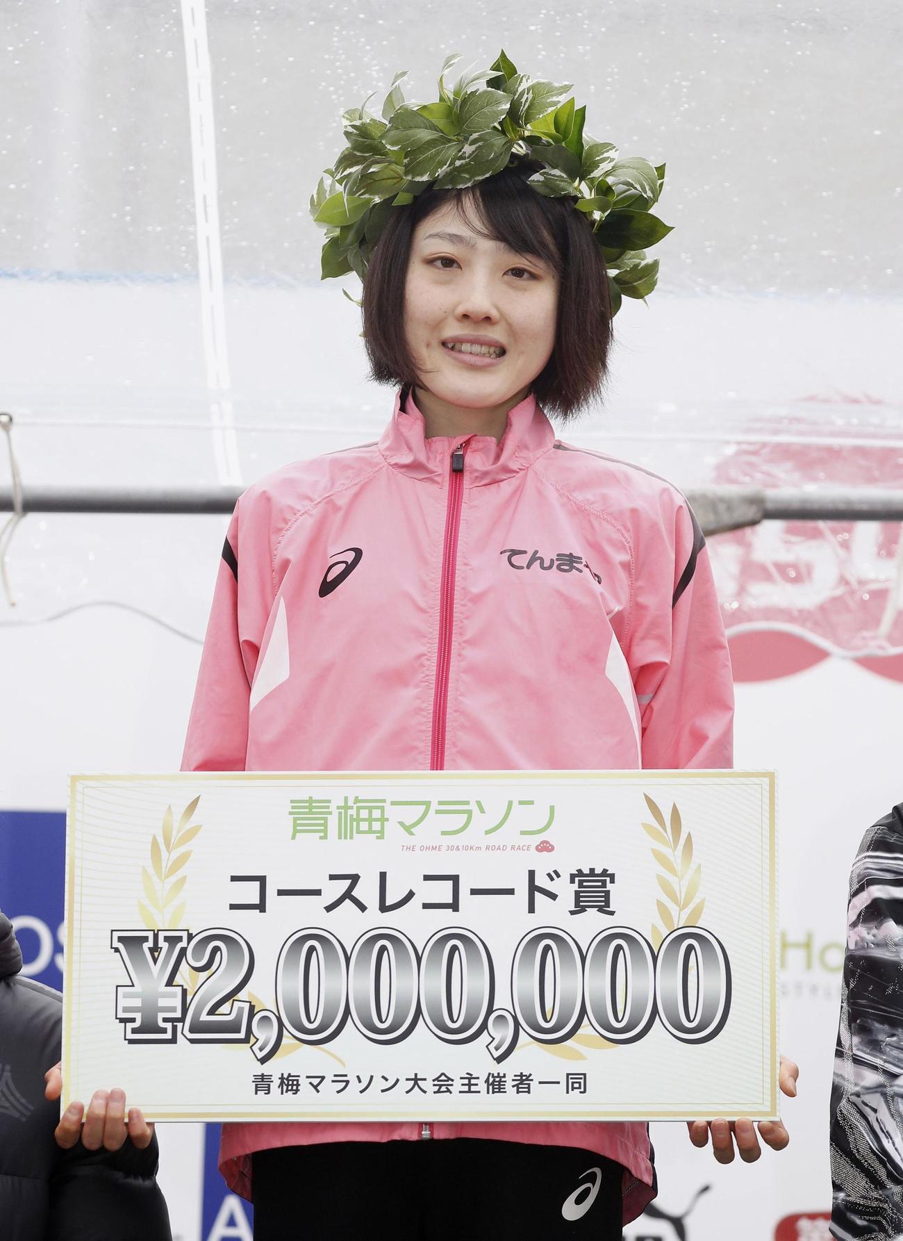 青梅マラソンで日本新記録をマークして優勝し、表彰式で笑顔を見せる前田穂南(共同)