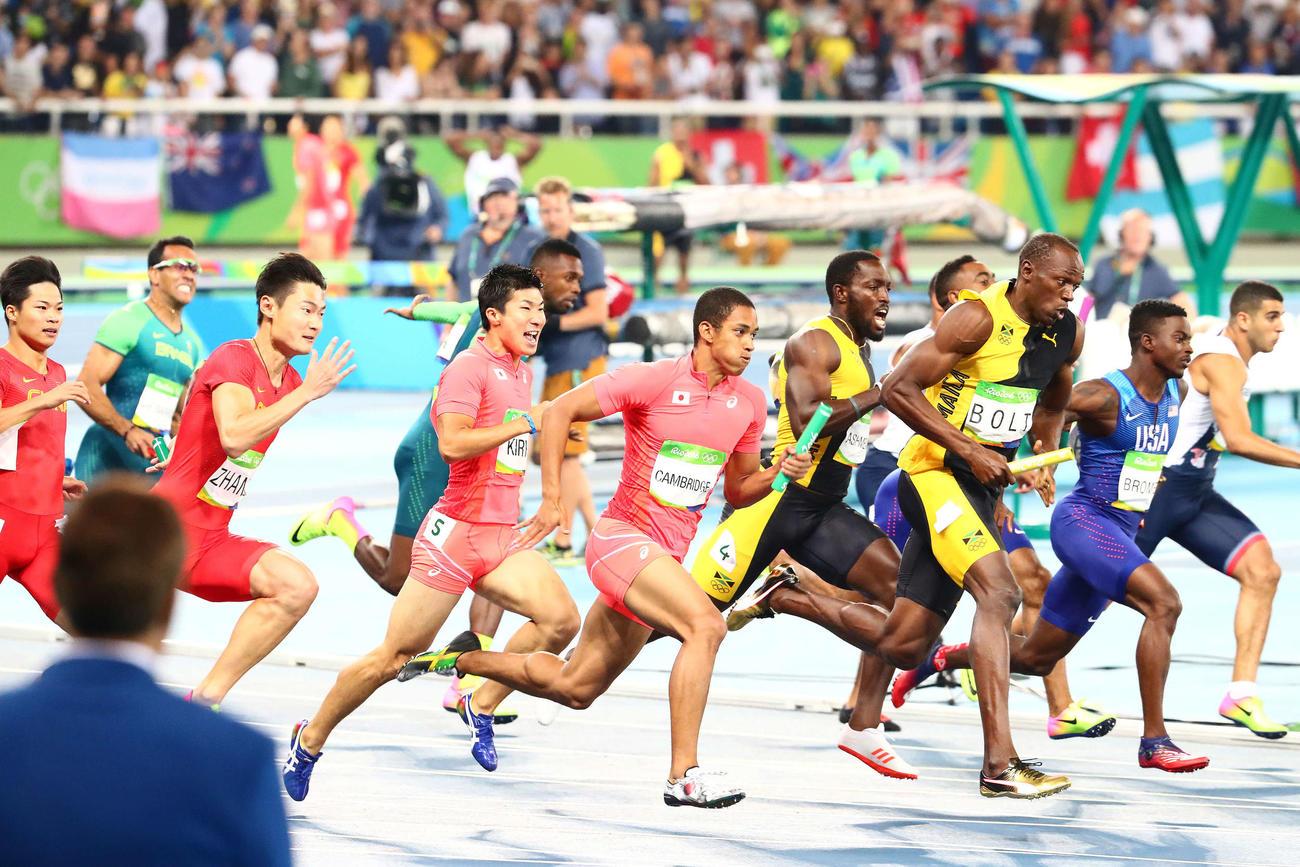 リオデジャネイロ五輪 男子400メートルリレー決勝で4走のケンブリッジ飛鳥にバトンを渡す3走の桐生祥秀(左から4人目)。右から3人目はウサイン・ボルト(2016年8月19日撮影)