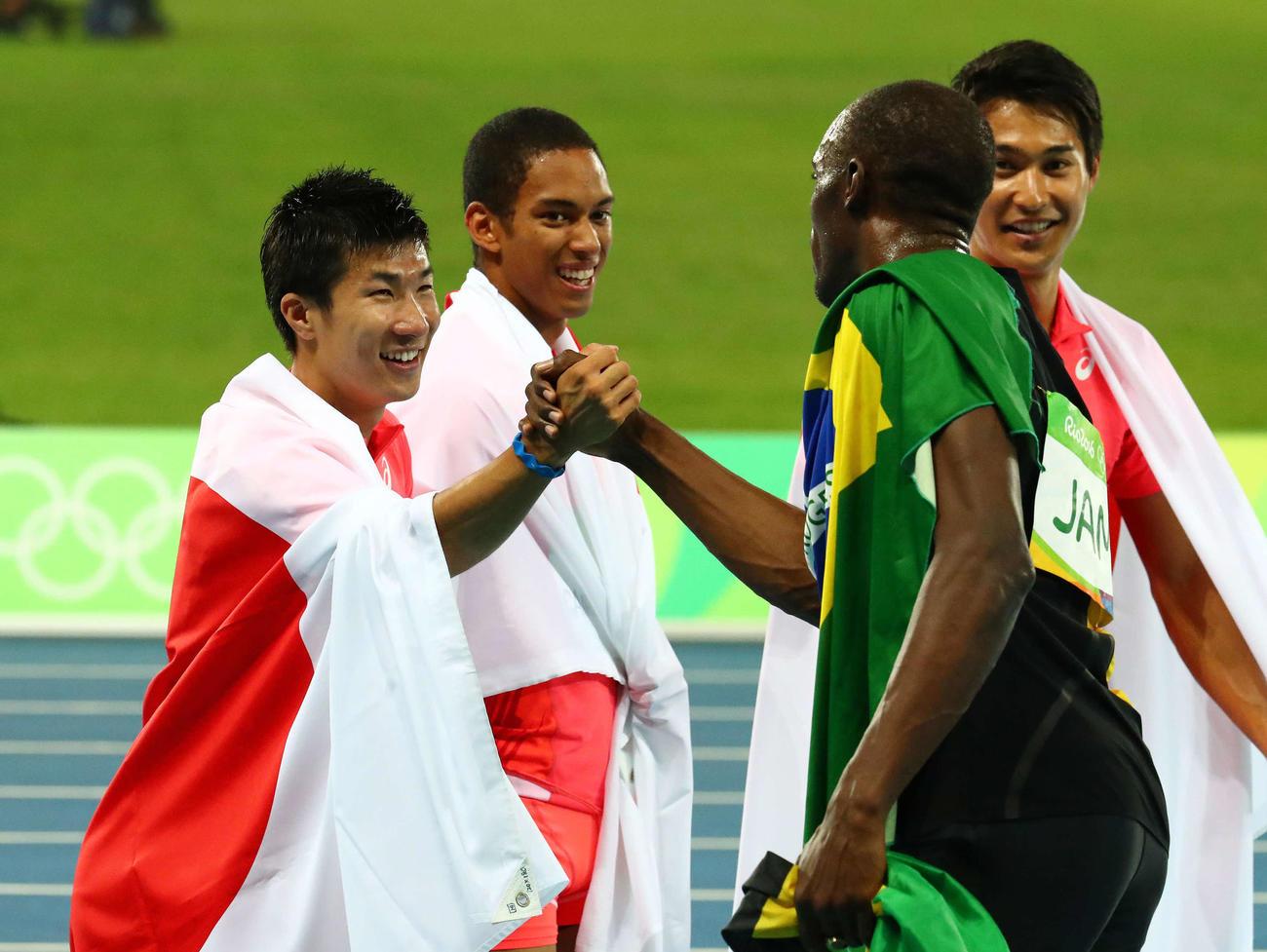 男子400メートルリレー決勝 優勝したジャマイカのボルト(右)と握手をかわす桐生。後方左からケンブリッジ、飯塚(2016年8月19日撮影)