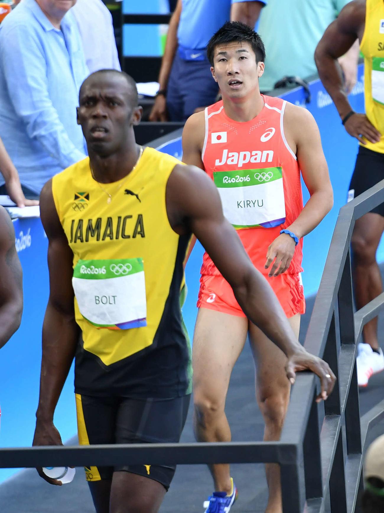 リオデジャネイロ五輪、男子100メートル1次予選7組 同組4位となりミックスゾーンに向かう桐生。手前はボルト(2016年8月13日撮影)