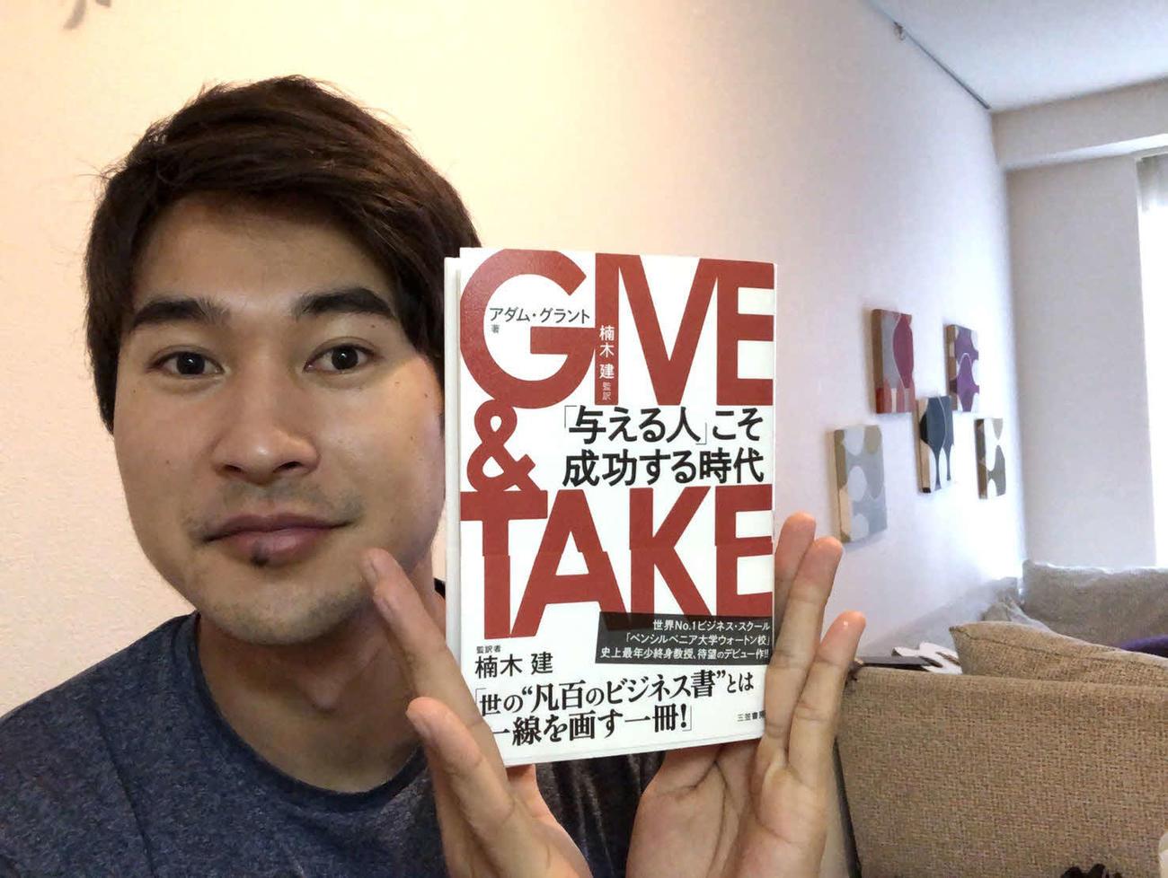 愛読書『GIVE & TAKE「与える人」こそ成功する時代』を手にする陸上・飯塚翔太