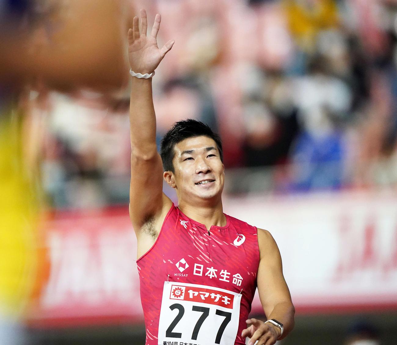 男子100メートルで優勝しスタンドに手を上げる桐生(撮影・江口和貴)