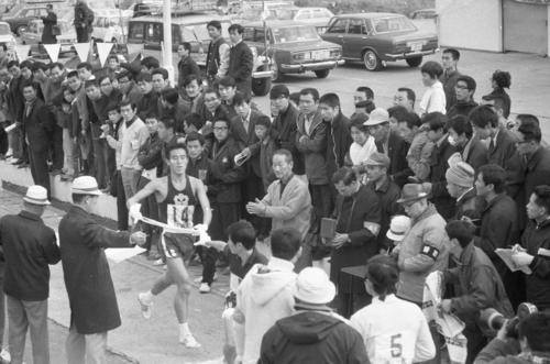 往路5区小田原中継所 4区小沢欽一(左=2年)から5区松岡厚(4年)にトップでタスキリレーする日体大=1970年1月2日