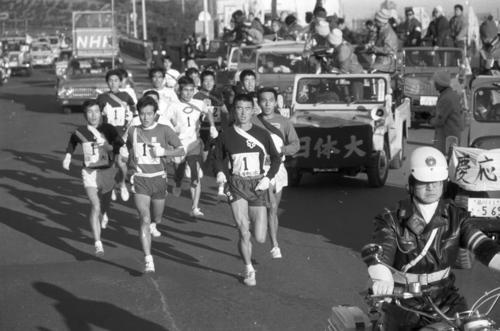 往路1区 日比谷通りを行く一団、トップは日体大・伊藤保(4年、区間4位)。5年ぶり出場の慶大伴走車(右)も=1971年1月2日