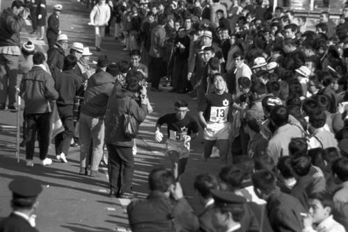 路5区小田原中継所 日大(左奥)に2秒差をつけトップを奪い返しタスキリレーした国士舘大4区今野幸昭(右=2年、区間1位)と5区大花務(手前左=3年)=1971年1月2日