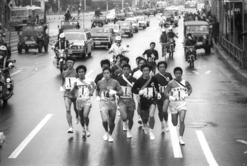 往路1区 第一京浜を行く集団。手前左から東京農大・小菅勝己(3年、区間5位)、大東大・橋口弘(2年、区間2位)、日体大・石井隆士(2年、区間8位)、国士舘大・橋口憲一(2年、区間7位)、東海大・川島二郎(1年、区間10位)=1975年1月2日