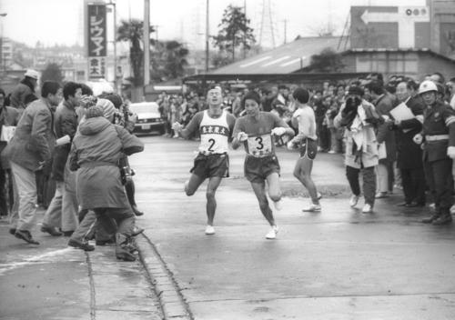 往路3区戸塚中継所 1位と1分26秒差の5位でタスキをもらった前年「12人抜き」の東京農大・服部誠(左=4年)は、順天堂大、専大、大東大に続きトップ筑波大も抜き、1時間13分21秒の区間新で3区山本吉光(右=2年)へタスキリレー=1975年1月2日