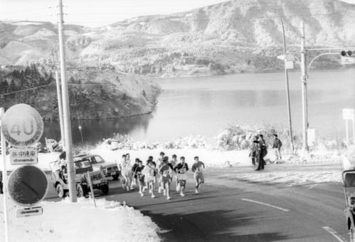 復路6区 午前8時、からりと晴れた芦ノ湖畔駐車場を一斉スタートした15校は、芦ノ湖をバックに登りにかかる=1975年1月3日