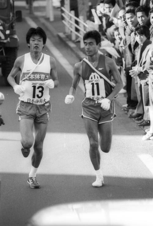 復路7区 6区谷口浩美が34秒差まで縮めた日体大は、7区前田直樹(左=3年、区間1位)が酒匂橋手前の6キロ地点で、順天堂大・村松学(右=4年、区間2位)をとらえ抜き去る=1981年1月3日