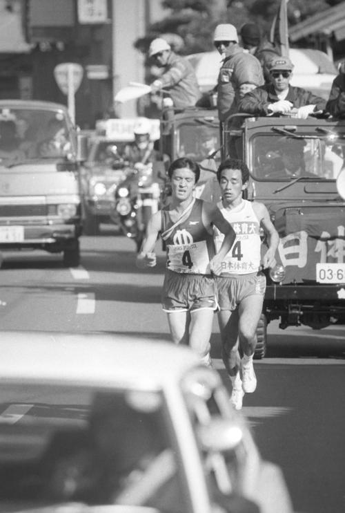 往路4区 日体大・島村雅浩(右=3年、区間3位)は、順天堂大・中島修三(左=3年、区間1位)に追いつかれるが、日体大は順天堂大の伴走車を間に入れないまま6キロも故意に並走させ、ラストスパートで再び引き離す=1982年1月2日