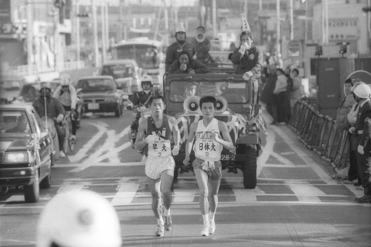 往路2区 3位でタスキをもらった早大・遠藤司(左=4年、区間2位)は、9秒差の東海大をあっという間に抜き、京急・戸部駅のガード下で日体大・中田盛之(右=4年、区間9位)をとらえ並走、この後10キロ過ぎに引き離す=1985年1月2日
