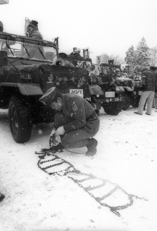 復路6区 7年ぶりの雪で急きょチェーンをつける亜大の伴走車=1985年1月3日