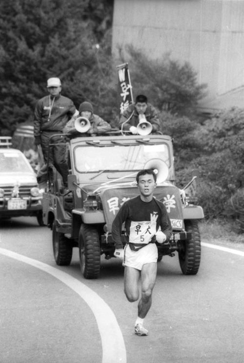 往路5区 伴走車に乗った遠藤司(中央=4年、2区2位)の声援を受けながら3度目の箱根の山を快走、1時間11分59秒の区間新で首位を堅守した早大・木下哲彦(3年)=1985年1月2日