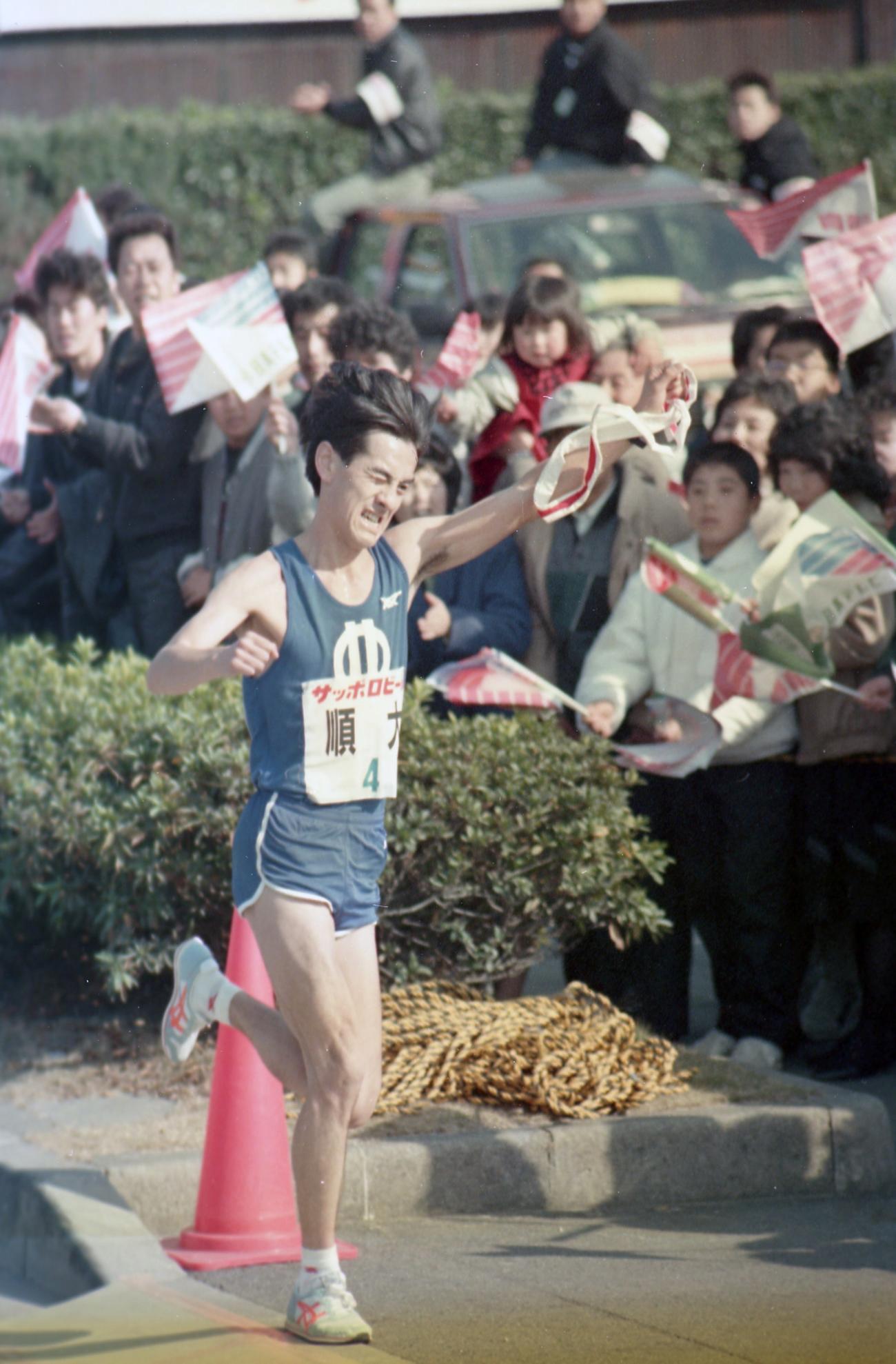 往路4区 2位大東大に3分27秒と差を広げタスキリレーに入る順天堂大・石原典泰(4年、区間1位)=1988年1月2日