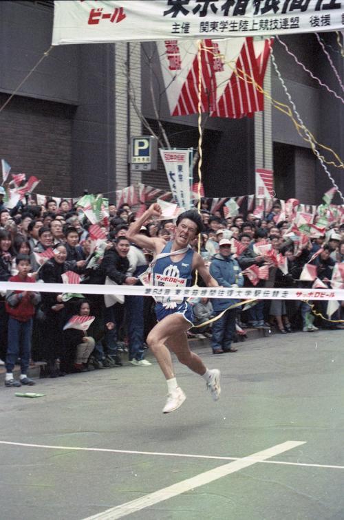復路10区読売新聞社前 史上最高タイムの11時間4分11秒で3年連続7度目の優勝テープを切る順天堂大アンカー山田和人(2年、区間1位)=1988年1月3日