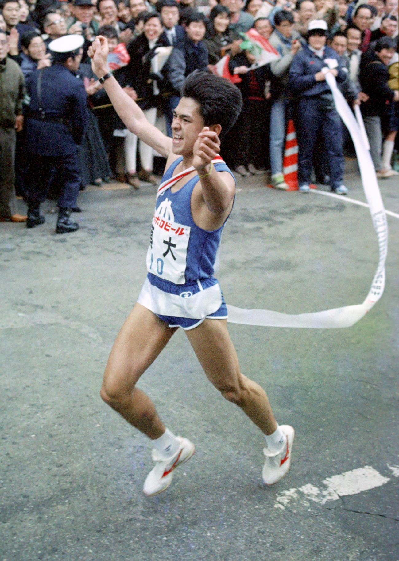 復路10区 順大のアンカー、1年生の巽博和は好走して優勝のゴール。テープを巻きつけながら喜びに沸く僚友の輪に飛び込んだ=1989年1月3日