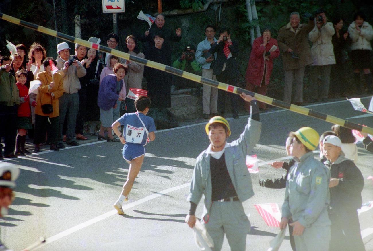 往路5区 手で上げた箱根鉄道小涌谷踏切を渡ったトップの順天堂大・仲村明(3年、区間2位)=1989年1月2日